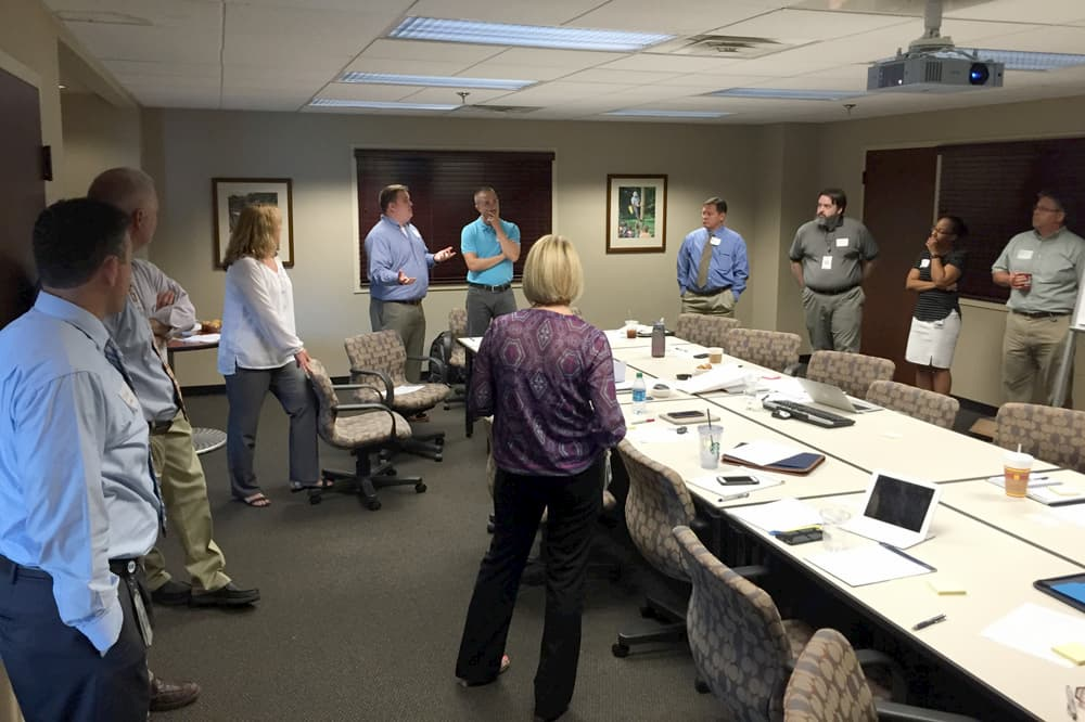 A team stands around a conference room in discussion during a Discovery