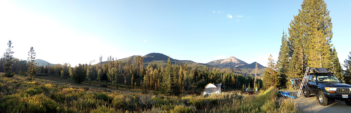 Campground campsite in the Rocky Mountains with tent being pitched